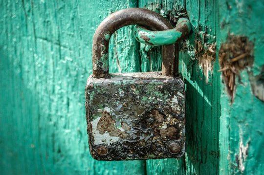 Bild på ett låst rostig hänglås mot en turkos trädörr