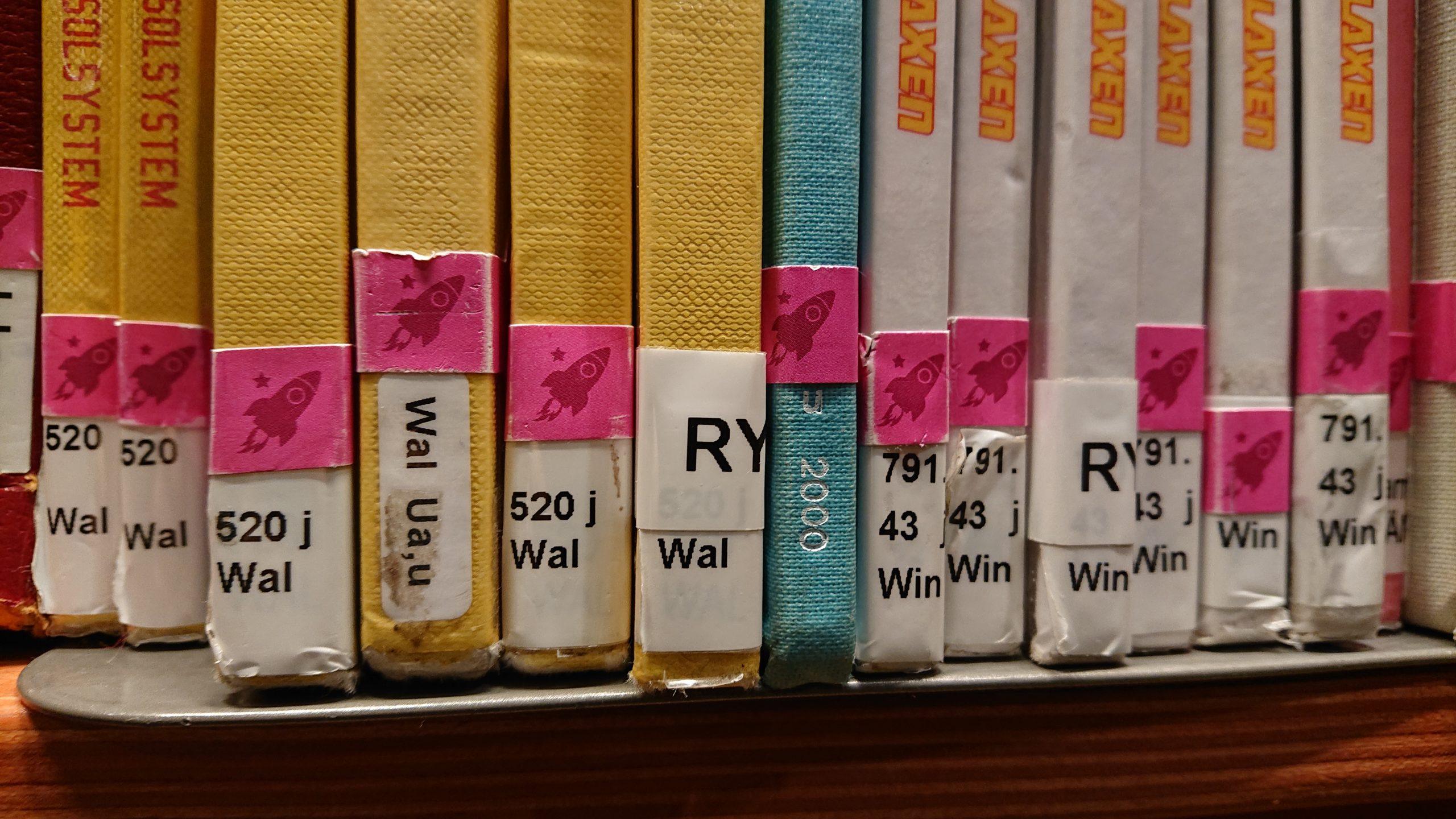 """En halv hyllmeter böcker från barnavdelningen. Bibliotikarierna har satt egna """"pluppar"""" i form av raketer som visar att det är böcker med science fiction-tema"""