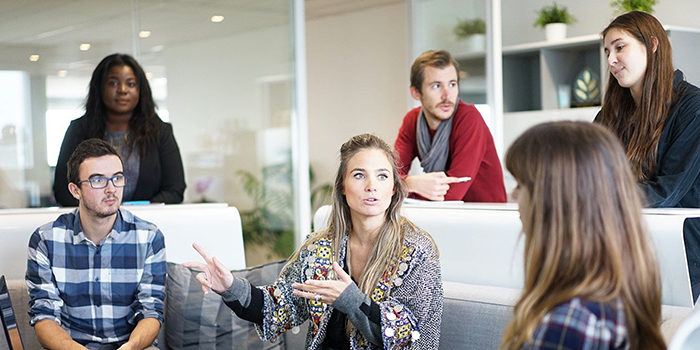 Sex person som har ett möte och diskuterar