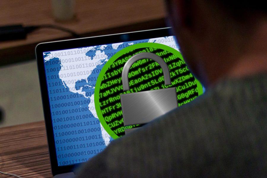 En dataskärm sedd över axeln på anonym användare. På skärmen en ikon som visar krypterad text som täcks av ett stort hänglås
