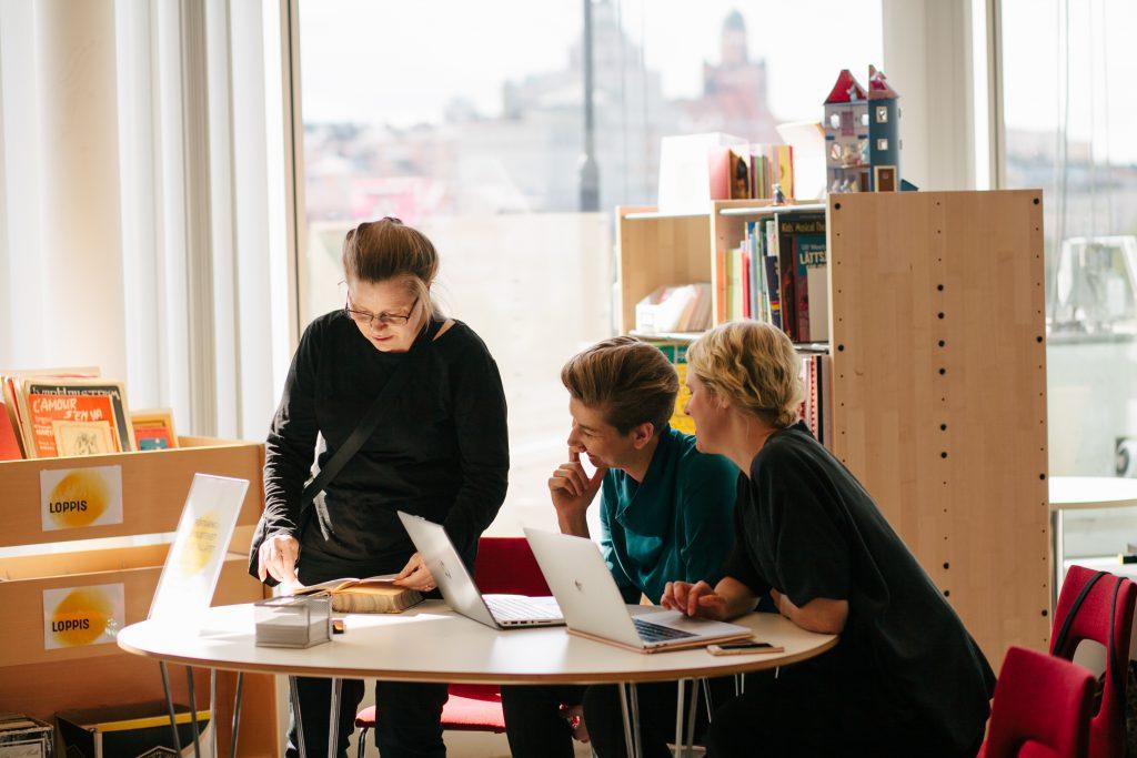 Rre personer med datorer på ett bibliotek