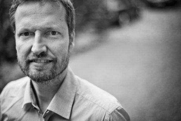 Svartvit porträttbild på Mikael Klintman.