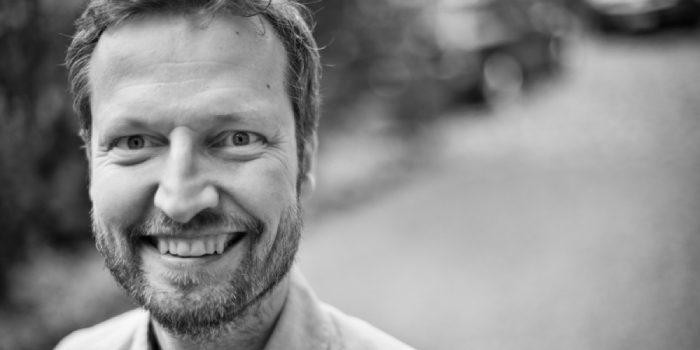 Svartvitt porträttbild av Mikael Klintman, en medelåldersman med kort hår och kort skägg.