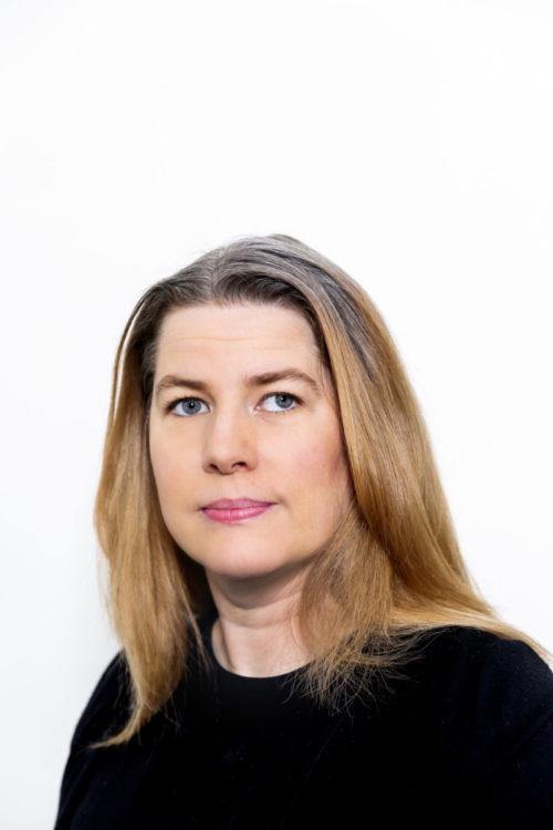 Portträttbild på Åsa Larsson. En kvinna med långt cendréfärgat hår och svart tröja.