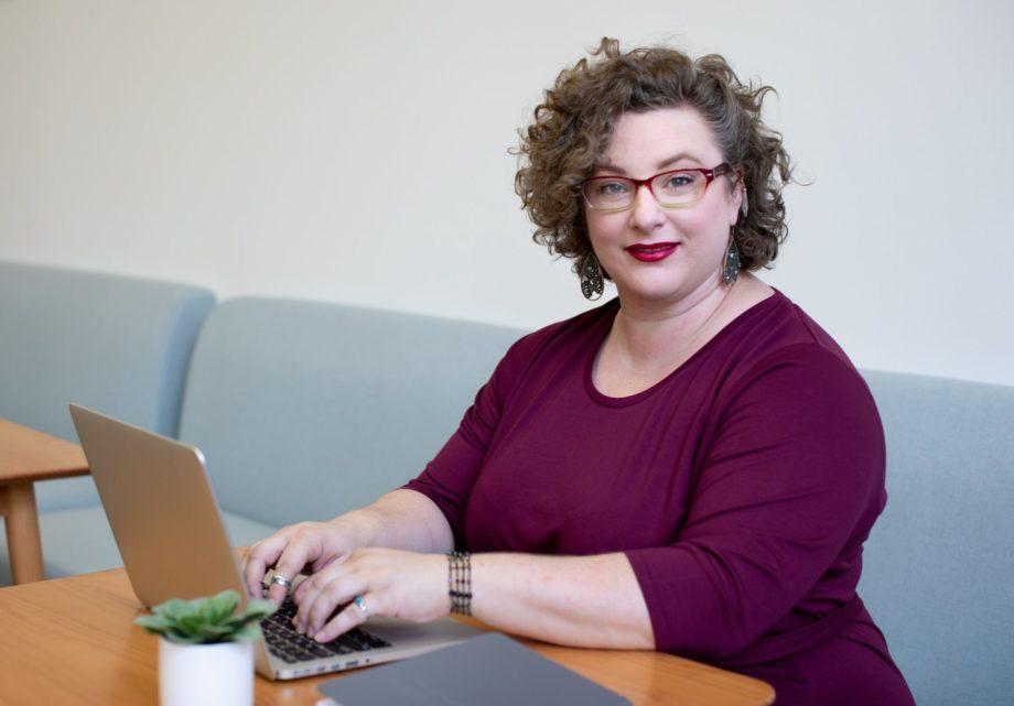 Kvinna i vinröd klänning sitter vid sin bärbara dator.