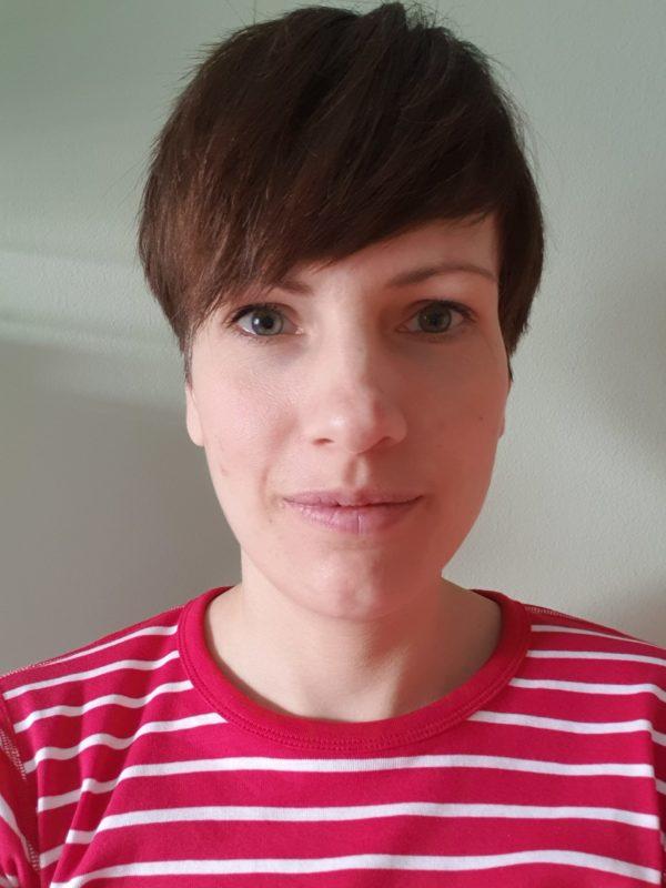 Portträttbild på Julia Sverke, en kvinna med kort brunt hår och rödrandig tröja.