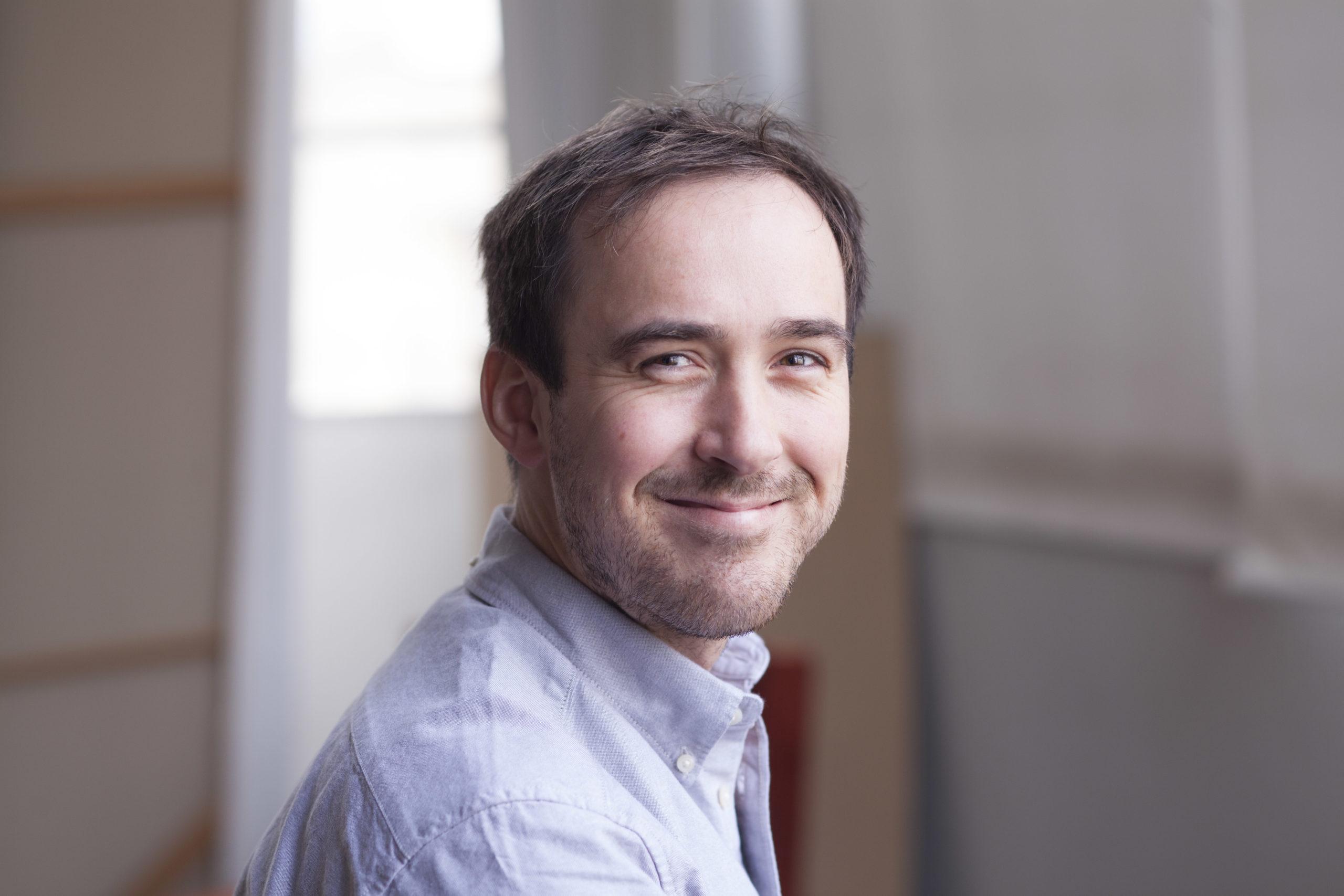 Portträttbild på Martin Törnros. En leende man i skjorta och med brunt hår.