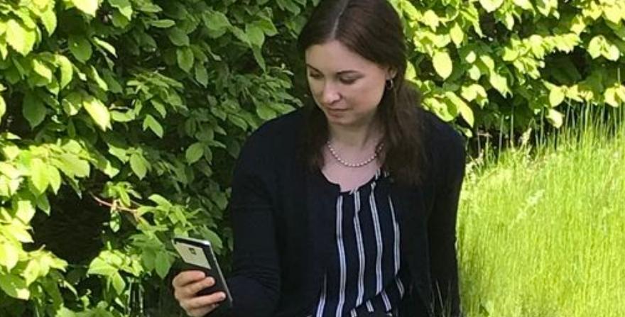 Kvinna som tittar på mobil.