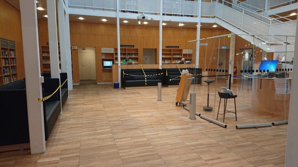 Tom läsesesal från Malmö stadsbibibliotek. Avspärrade sittplatser och informationdisk avskärmad med plastskärmar