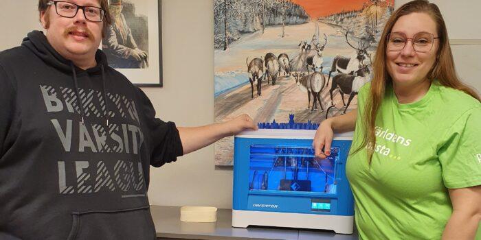 Bilden visar en man och en kvinna som står på varsin sida om en 3D-skrivare.