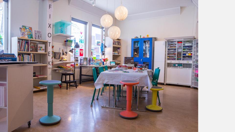 Ett makerspace med bokhylla med böcker, och hyllor med diverse material.