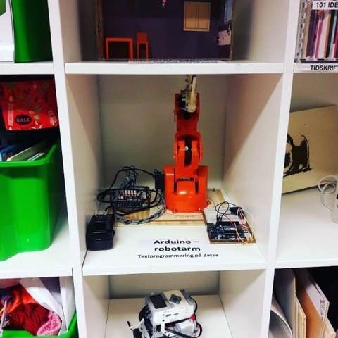 En bokhylla med en Arduino robotarm i.