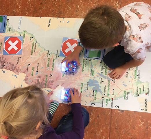 Två barn som kör rboten Bluebot på en karta över Sverige.