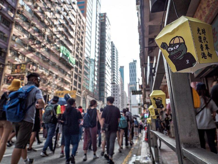 Demonstranter i Hong Kong marscherar med bilder av Pepe som har en knuten näve, som i protest